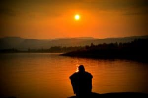 man reflecting at lake's edge representing enneagram and fear